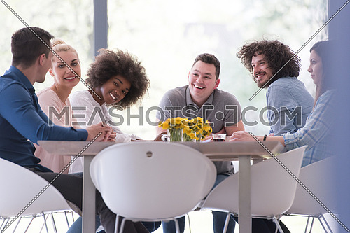 Multiethnic startup business team on meeting in modern bright office interior brainstorming, working on laptop and tablet computer