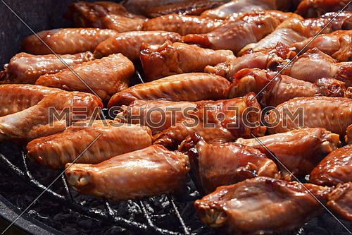 Chicken buffalo or teriyaki sauce raw wings cooked grilled on bbq smoke round grill, close up