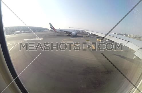 shot from plane window showing wing and runway while the plane is moving