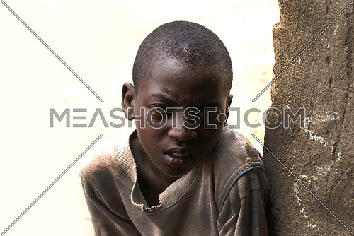 A sad african boy looking towards the camera