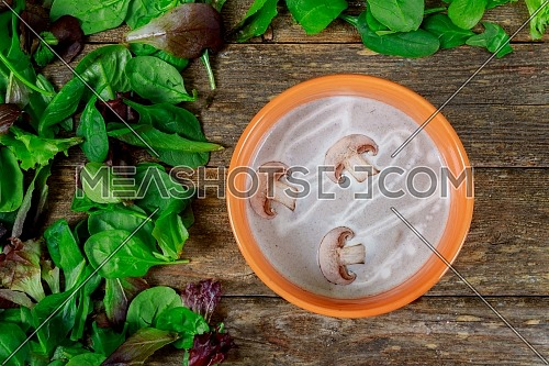 Cream soup of mushrooms with in purple bowl on a wooden table.