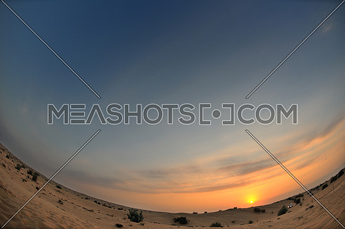 sunset with blue sky and clouds over sand dunes in sahara desert