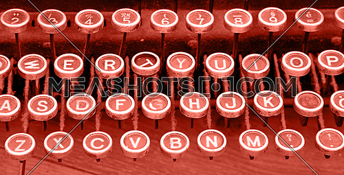 Close up coral pink color toned Latinic keyboard of old vintage antique typewriter with round buttons, high angle view, personal perspective