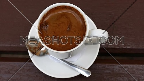 Close up one white cup full of Turkish black coffee and saucer on table with slow motion animated cinemagraph spin of coffee froth, elevated top view,