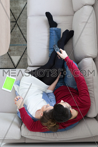 top view of Young couple on the sofa watching television together at home