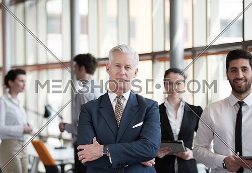 portrait of senior businessman as leader  at modern bright office interior, young  people group in background as team