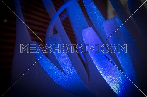 Close-up of blue abstract stripes of foamy material on dark background