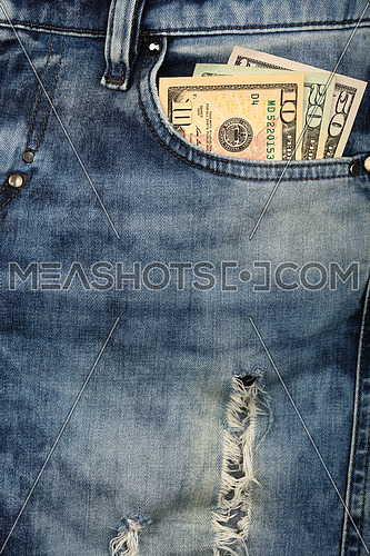 Close up several different value US dollar paper currency banknotes in jeans front pocket, low angle view