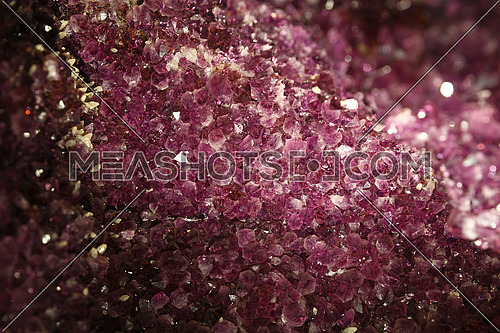 Close up background of vivid purple amethyst crystals geode bright lit in the dark