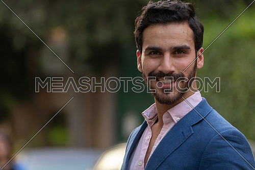 Mid-shot an elegant man walking in the the street in formal suit in blue at day