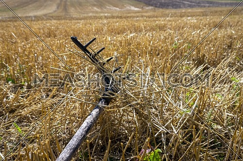 Rustic rake in a harvested field of wheat with stalk stubble in an agricultural landscape