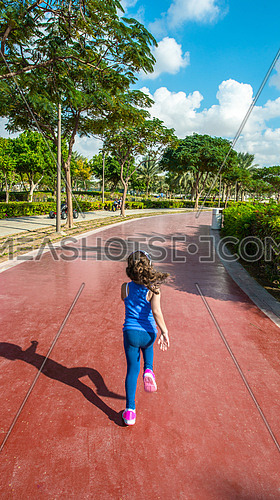 A little girl running on a track