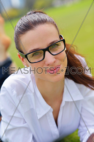 Young student woman reading a book and study in the park