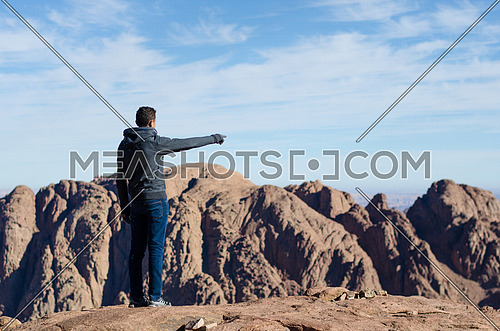 a man on the top of the mountain looking at the horizon