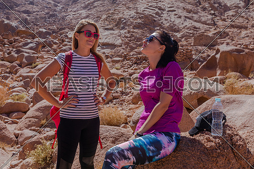 Long shot for two female tourists exploring at Sinai Mountain for wadi Freij at day.