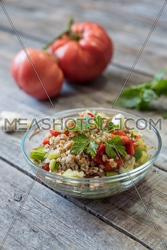 Lemon herbed cooked quinoa salad in a bowl on wooden table. Selective focus. Shallow depth of field.