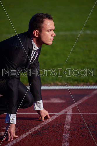 business man in start position ready to run and sprint on athletics racing track