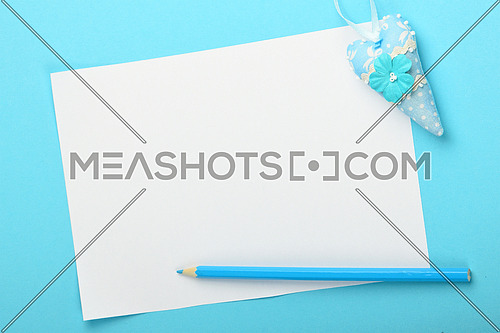 White paper note with small textile toy heart and pencil on tender blue background