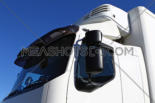 White tractor-trailer truck cab detail against blue skies