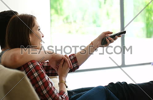 couple sitting in seperate sofas at home