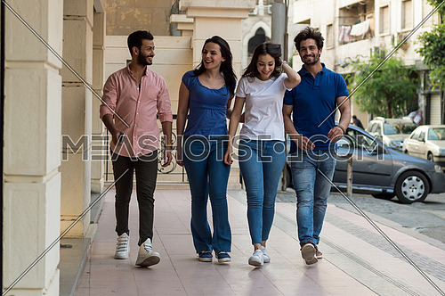 A group of young people speak and laugh as they walk in the street