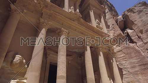 Low angle pan up of the Treasury facade in Petra