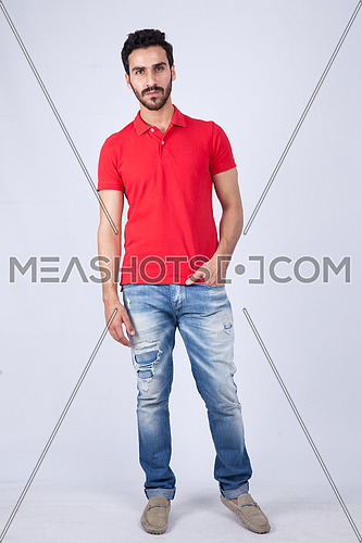 A young man wearing red t-shit posing on a white background