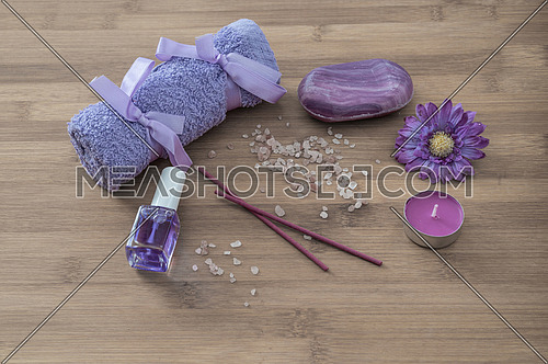 Spa concept. flowers,candles, aromatic salt,soap and bath purple towels on wooden background