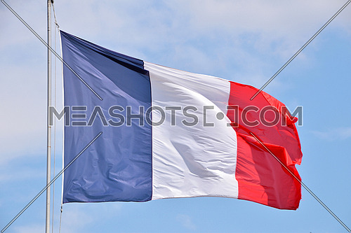 Close up flag of France waving and blowing in the wind over blue sky, low angle view