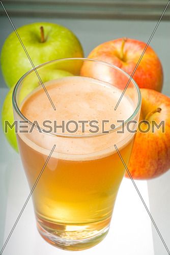 fresh  and healty natural apple  juice unfiltered , backlit on a light table