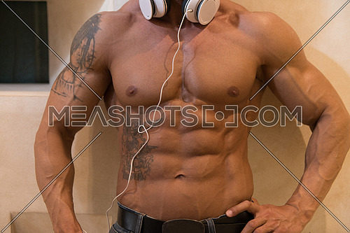 Muscular Mature Man Listening Music From His Mp3 Player In Modern Corridor Where He Poses