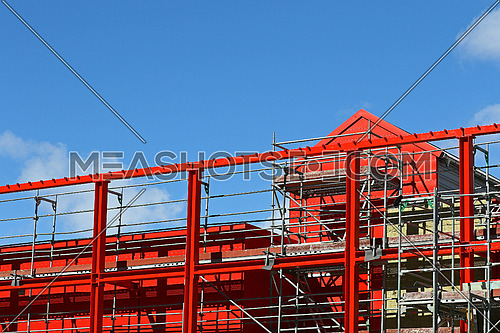 New steel beam construction being built against blue skies and white clouds