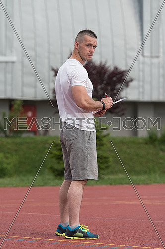 Portrait Of A Male Fitness Instructor Holding Clipboard Outdoor
