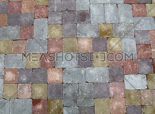 Background of street road colorful stone paving of multicolor bricks, close up, high angle view