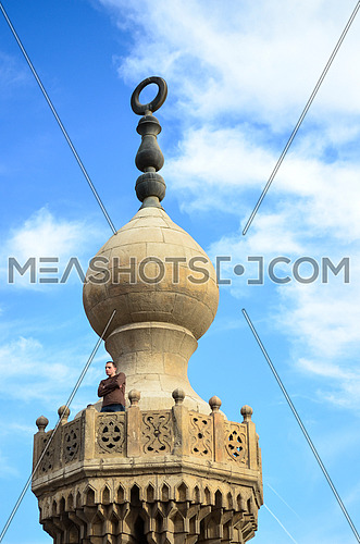 The top of a mosque minaret, old minaret goes back to the Mamlouki era and a man standing on the top floor.