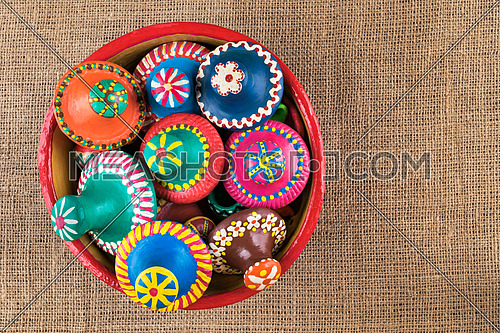 Pottery lids stacked in a pottery bowl on sackcloth background