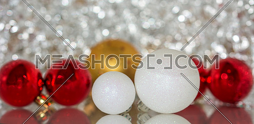 Colourful christmas baubles against a silver bokeh background