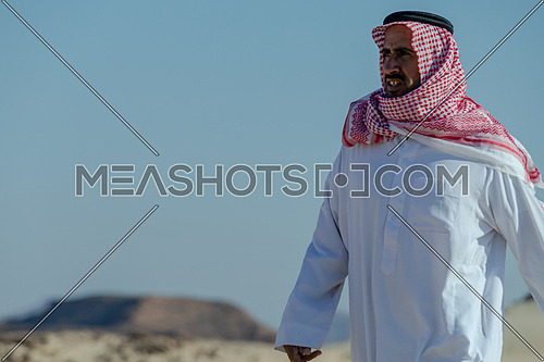 Portrait for bedouin male climbing down rocks by day.