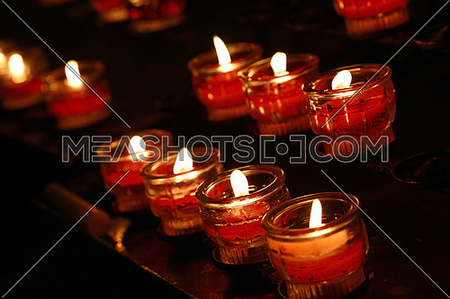Red translucent glass candles burning in dark church, close up, high angle view