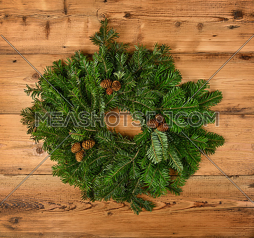 Close up Christmas wreath decoration of fresh green spruce branches with cones over wooden wall, front view