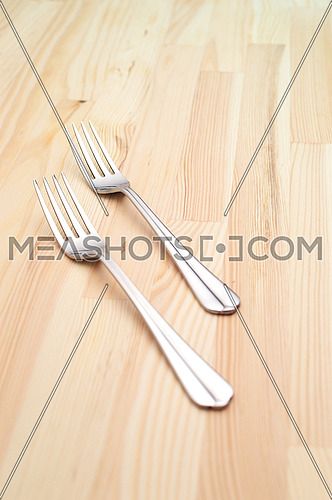 two fork on a kitchen pinewood table closeup