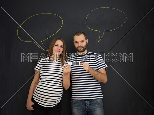 portrait of husband and pregnant wife posing against black chalk drawing board