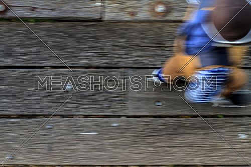 Fast moving man wearing casual clother on a wooden textured floor