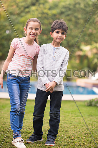 Portrait of a young middle eastern boy and girl in the yard by the pool on a sunny summer day
