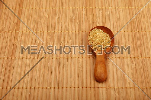 Wooden round scoop spoon of brown cane sugar on bamboo mat background