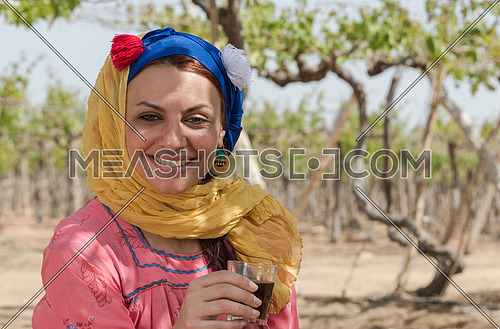 an egyptian female farmer taking a rest and drinking tea