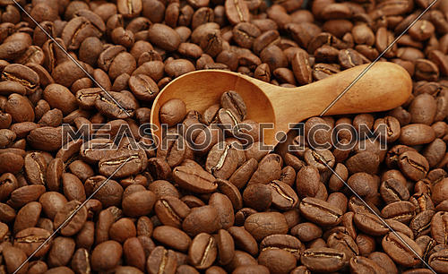 Close up wooden scoop with roasted coffee beans, elevated top view, high angle view