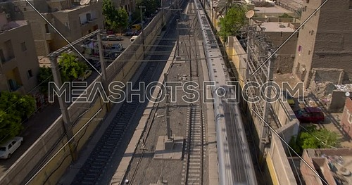 Aerial shot for Metro Passing by houses in Cairo at sunset