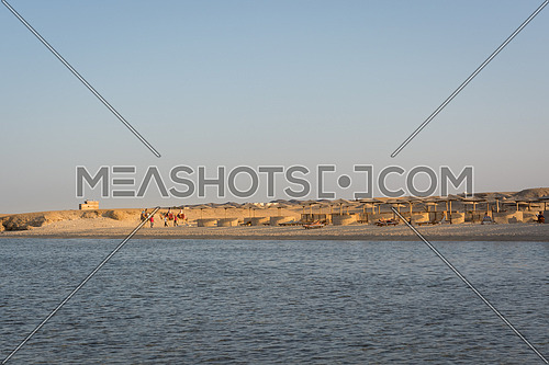 Egyptian beaches with typical parasols in the background and red sea in frontground.