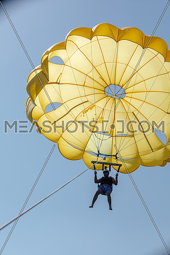Tourist parasailng in the Red Sea by day